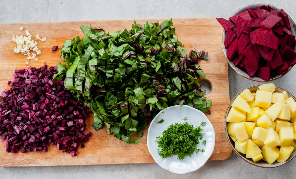 chopped beets, their stems and leaves, potatoes, dill and garlic on a chopping board