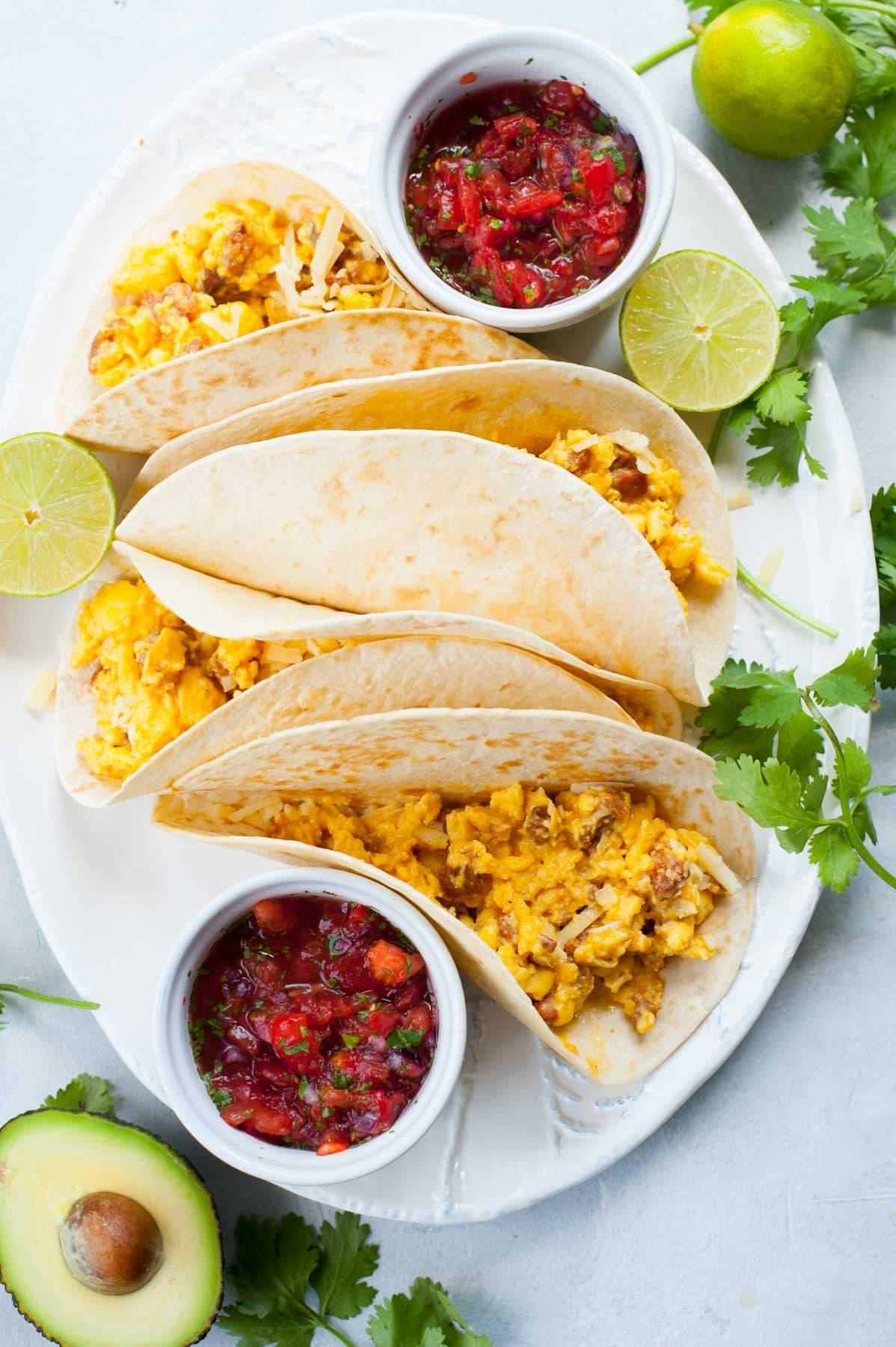 duży biały talerz z 4 tacos z jajecznica i chorizo, 2 małe miseczki z pico de gallo