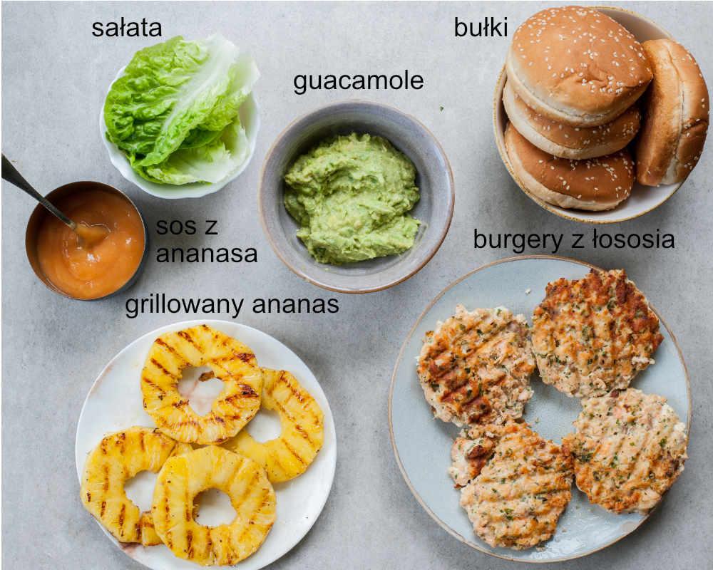 części składowe burgerów z łososiem (kotlety, bułki, guacamole, sałata, sos ananasowy, grillowany ananas)