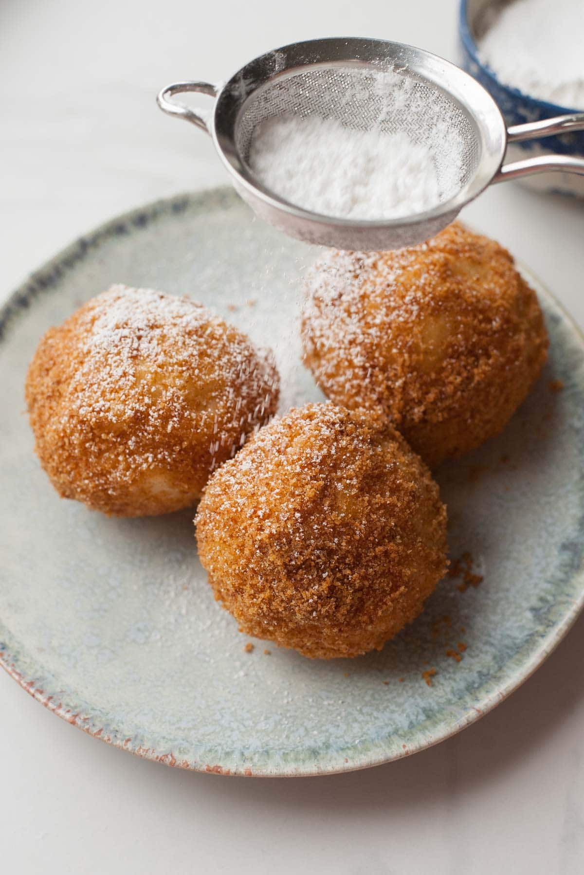 apricot dumplings on a green plate are being sprinkled with powedered sugar