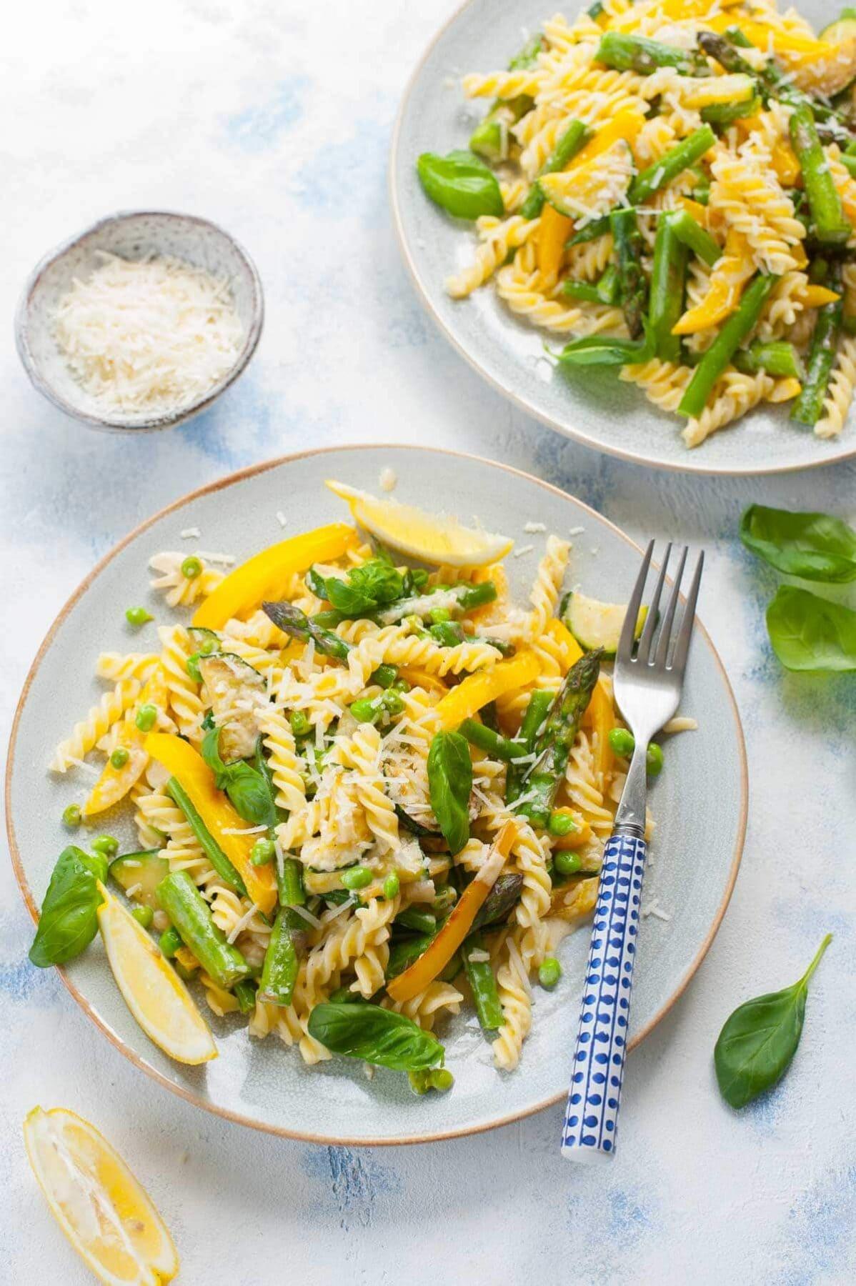 dwa talerze z makaronem z warzywami w kremowym sosie