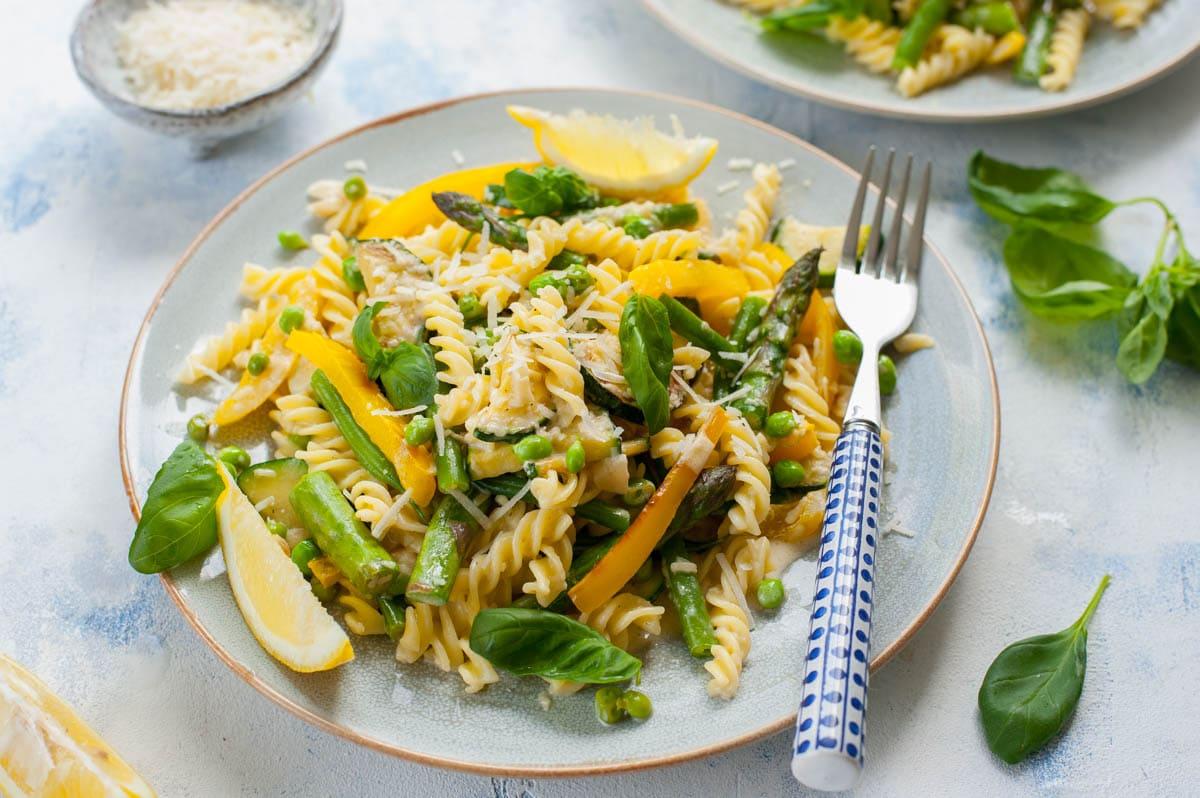 makaron z warzywami i kremowym sosem na niebieskim talerzu z niebieskim widelcem