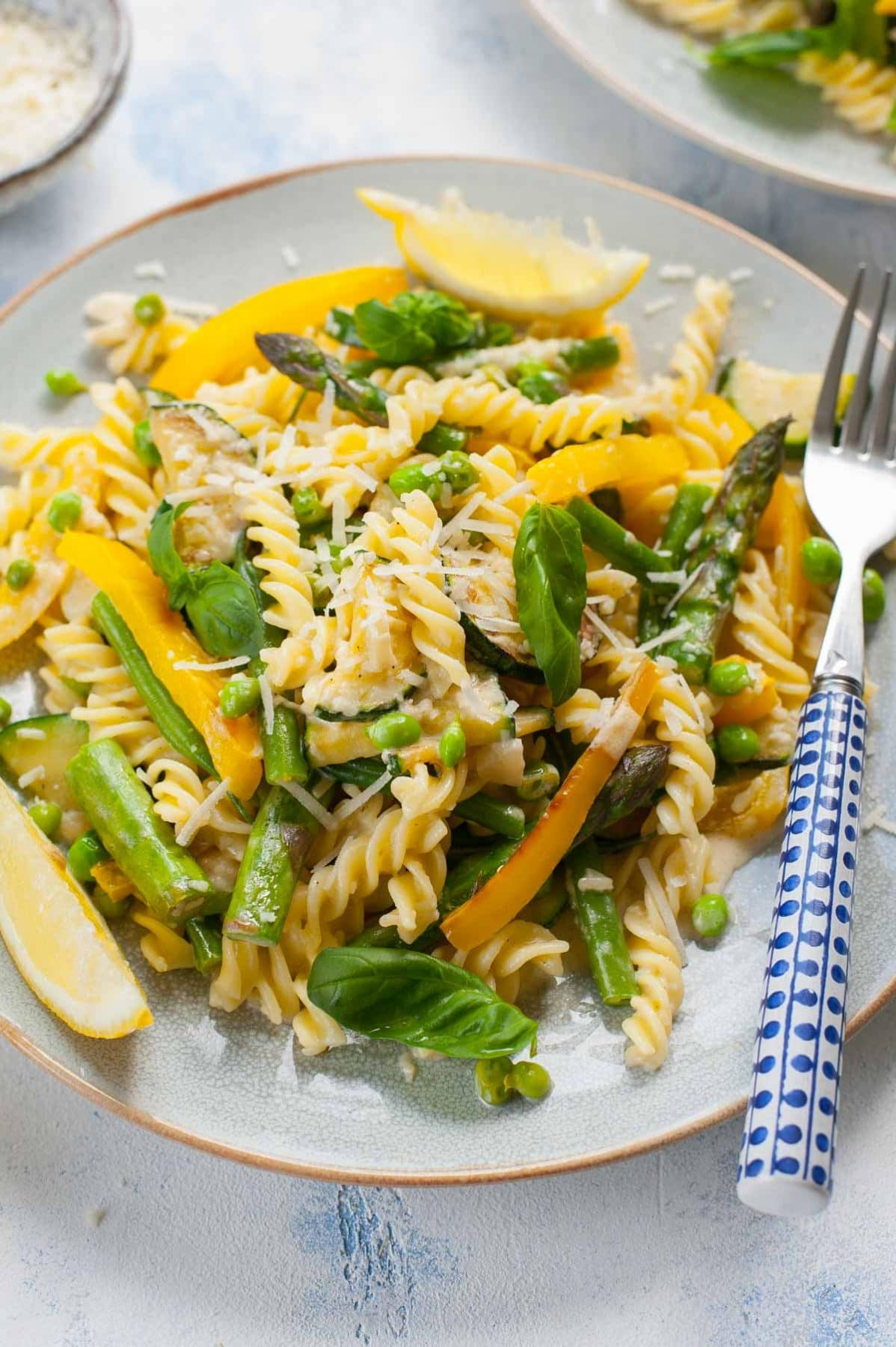 close up view on pasta primavera on a blue plate with a blue fork