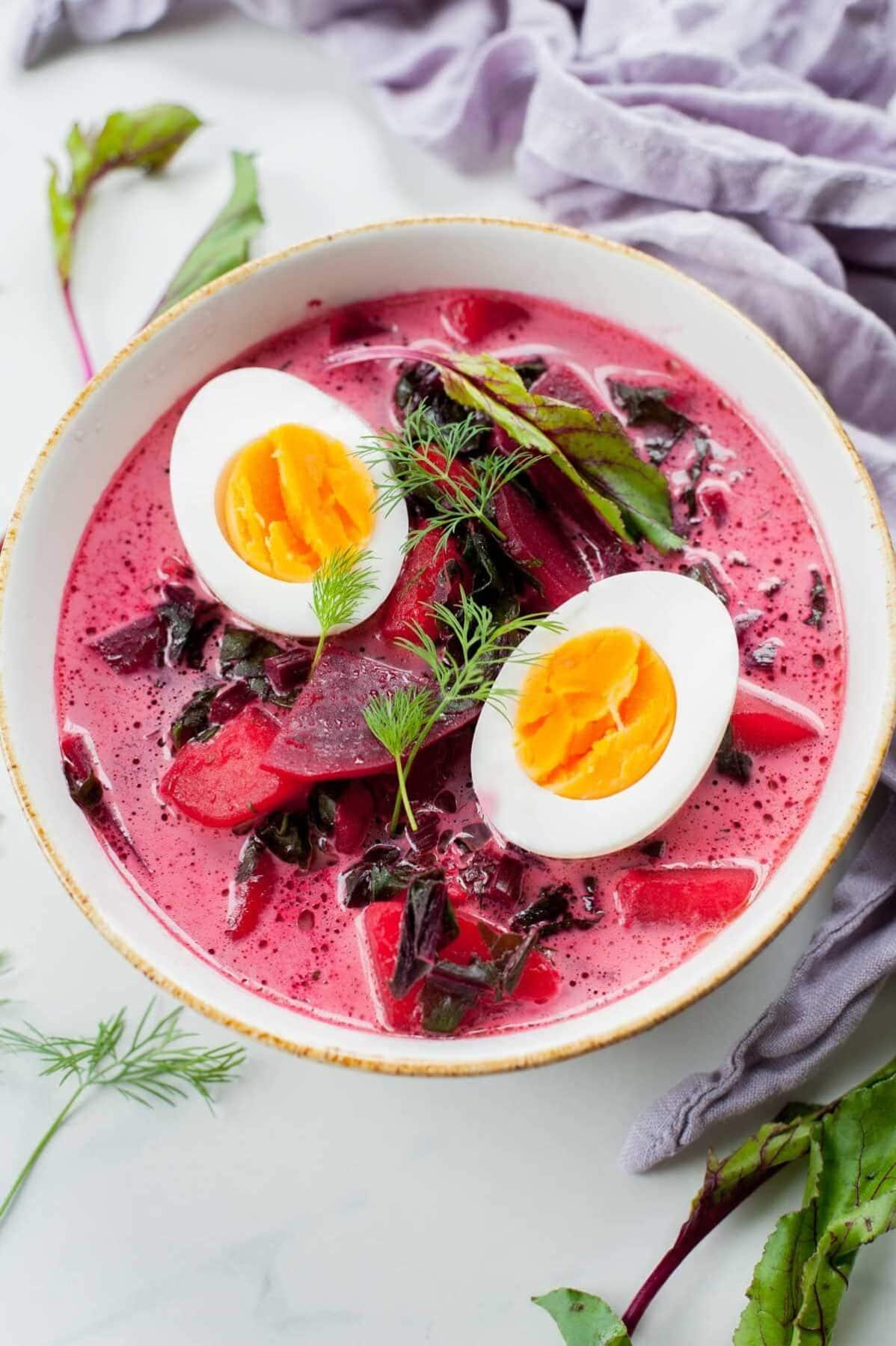 zupa botwinkowa z jajkami w białym talerzu, obok liście botwinki i gałązki koperku