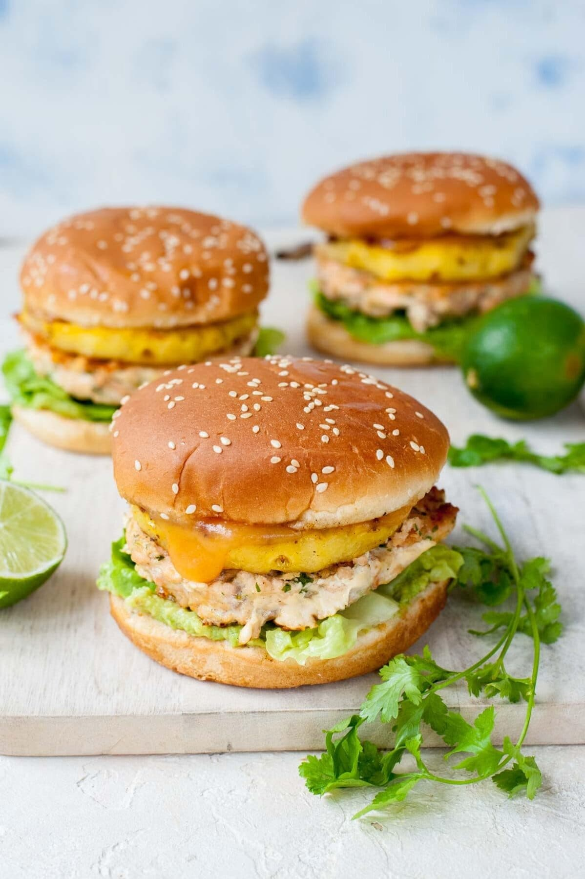 Three salmon burgers with pineapple and guacamole on a beige wooden chopping board.
