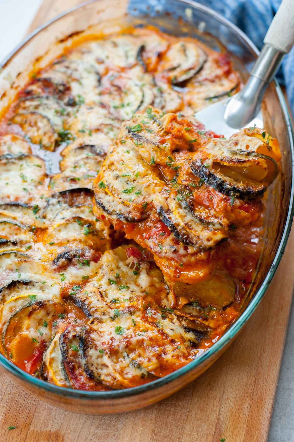 baked ratatouille in a baking dish being scooped with a metal spatula
