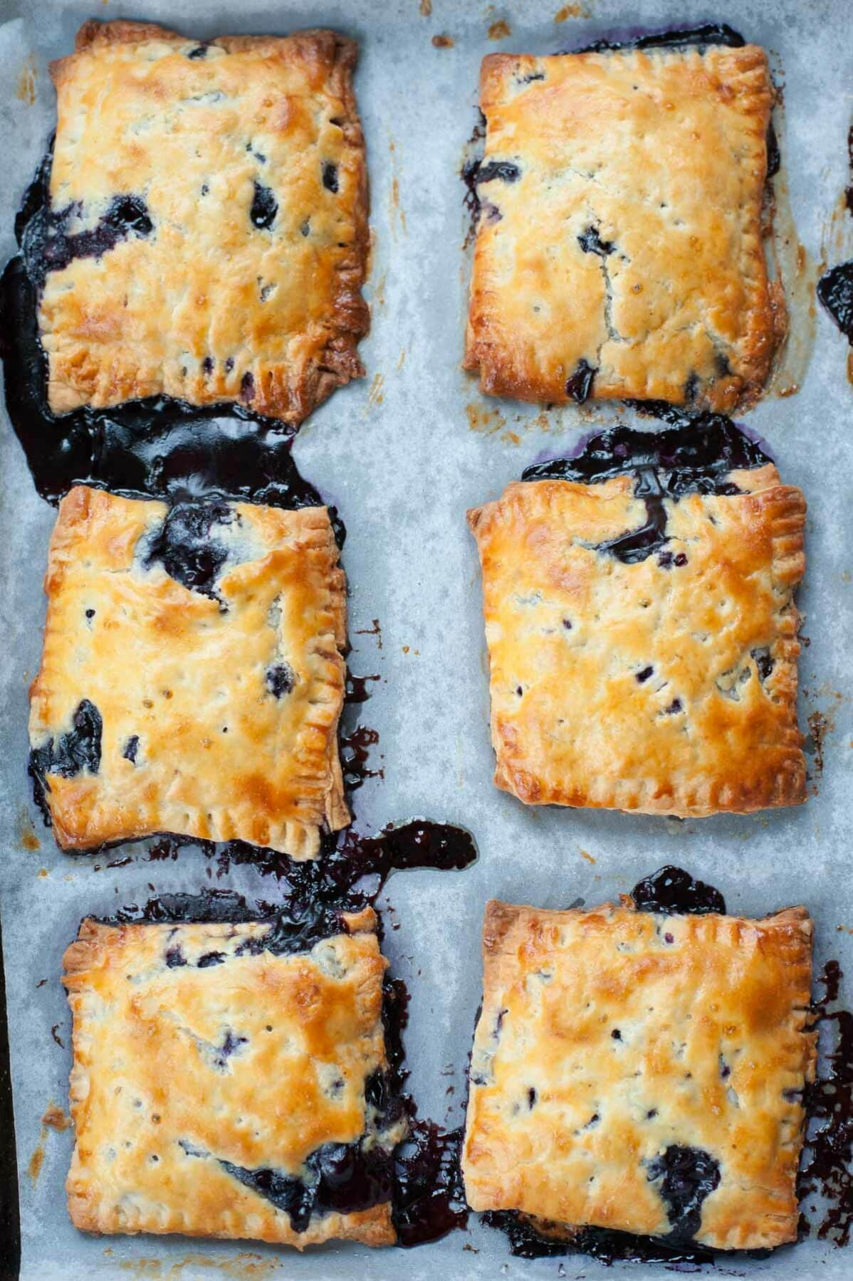 freshly baked blueberry hand pies on a baking paper