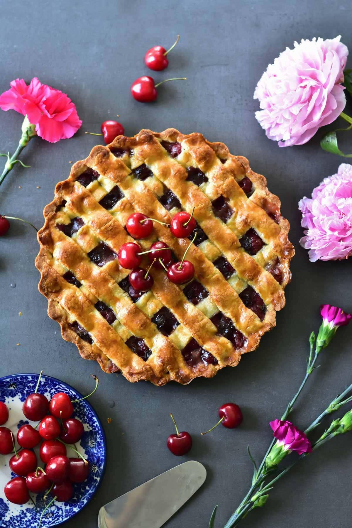 Tarta z czereśniami i czekoladą na ciemnym tle z czereśniami i kwiatami