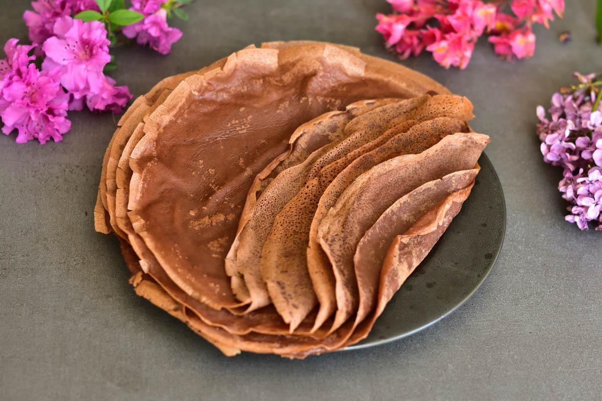 czekoladowe naleśniki na czarnym talerzu, w tle kwiaty