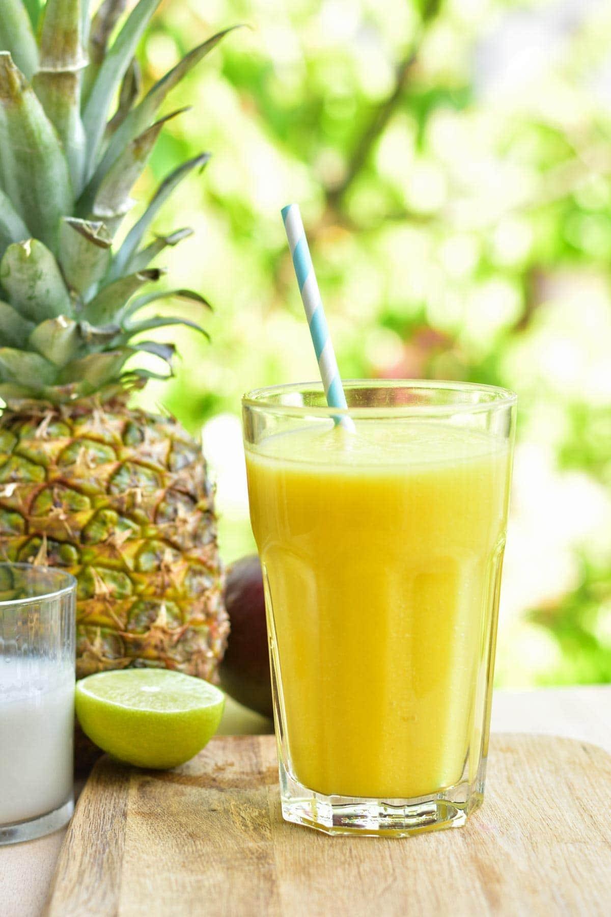 smoothie z ananasem, mango, mlekiem kokosowym i limonką w szklance na desce do krojenia