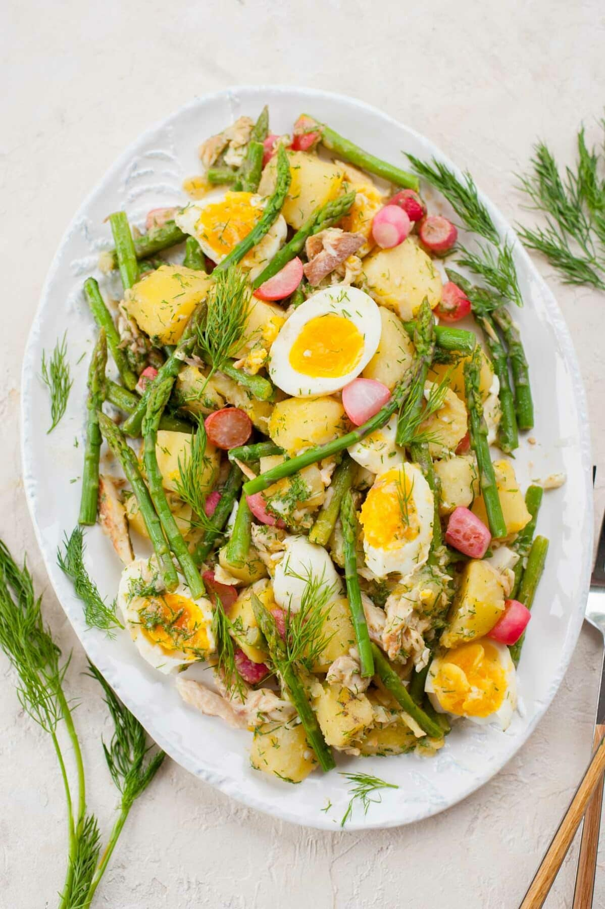 Potato and asparagus salad with eggs and smoked trout on a white plate