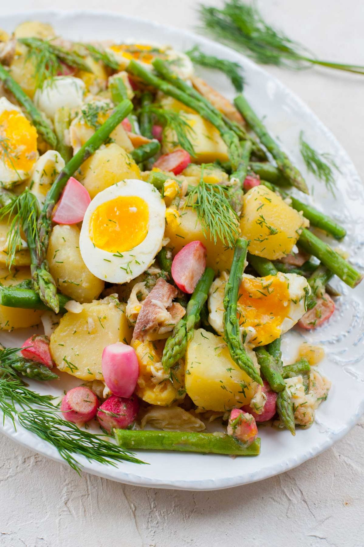 close up photo of potato and asparagus salad on a white plate
