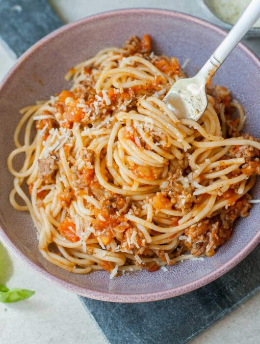 spaghetti with fresh tomato meat sauce on a fork in a violet bowl