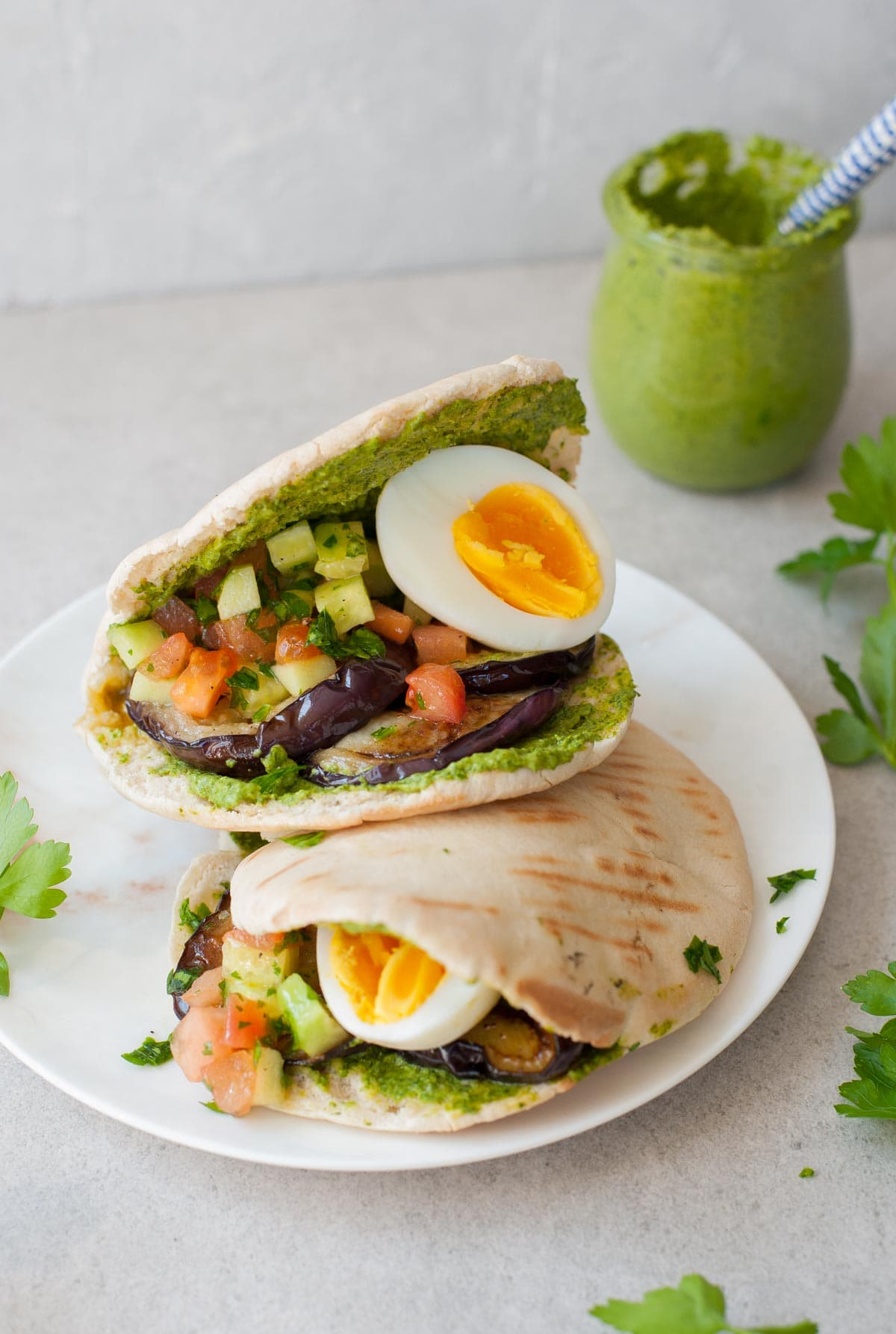 two pita breads filled with eggplant, eggs, tomato and cucumber salad, and green tahini sauce on a white plate