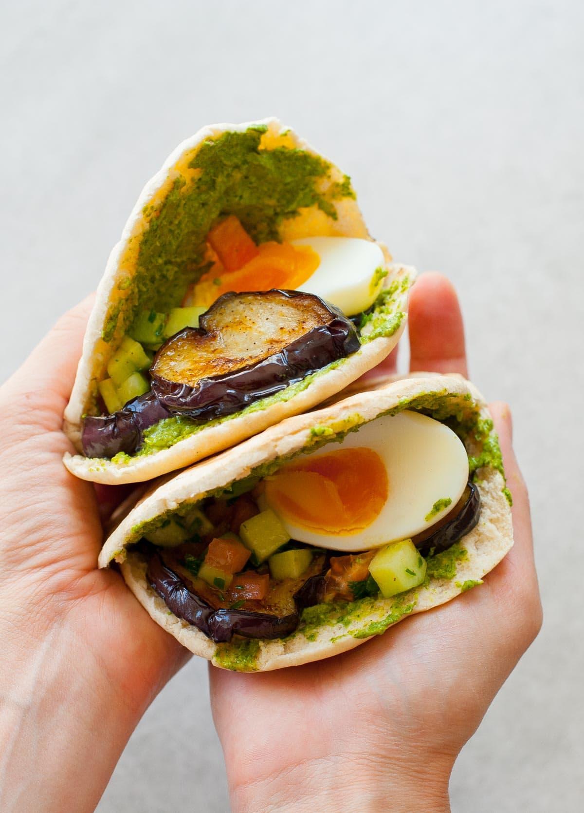 dwa chlebki pita z bakłażanem i jajkami trzymane w rękach