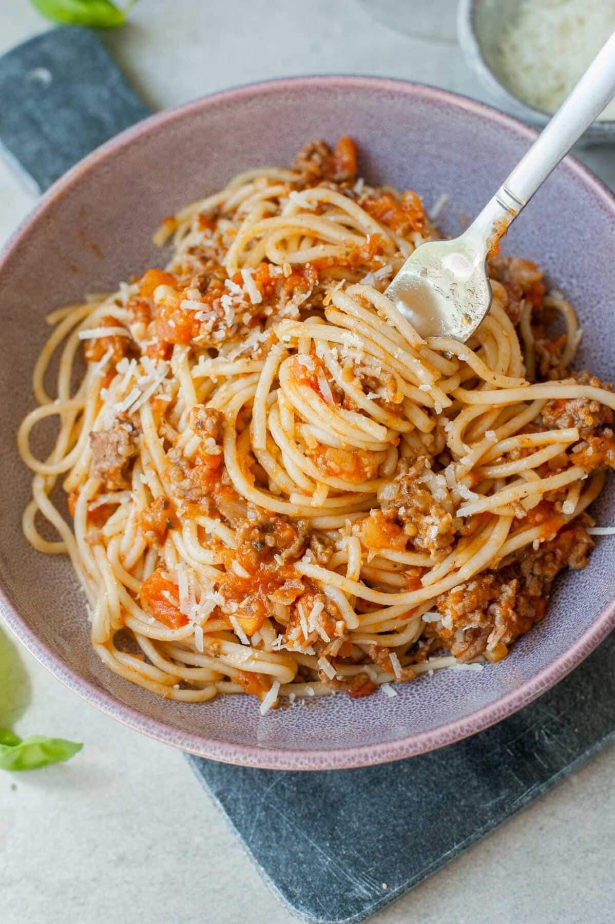 spaghetti z mięsem i sosem ze świeżych pomidorów nabite na widelec w fioletowej misce