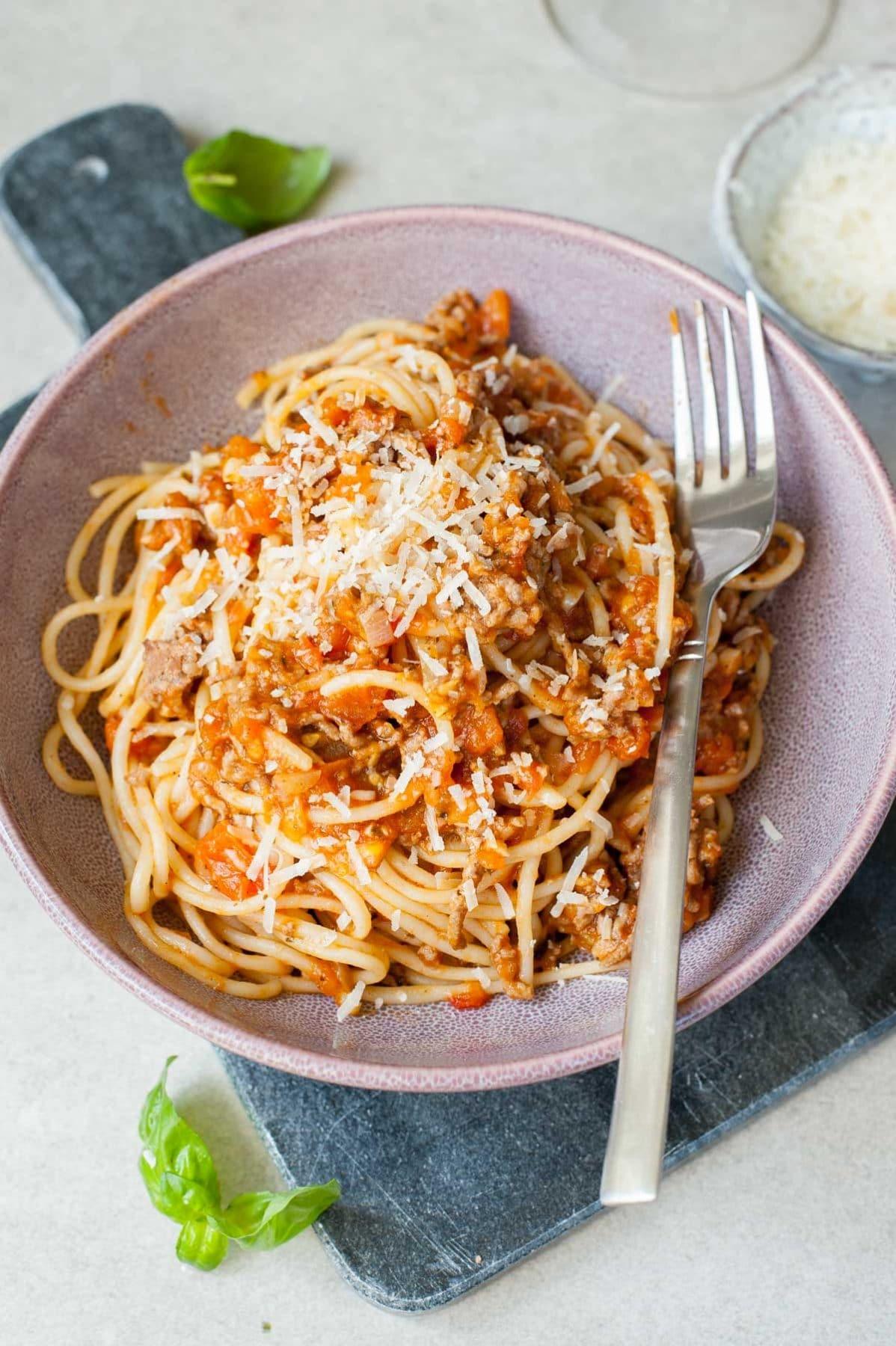 Szybkie spaghetti z mięsem i sosem ze świeżych pomidorów posypane parmezanem we fioletowej misce