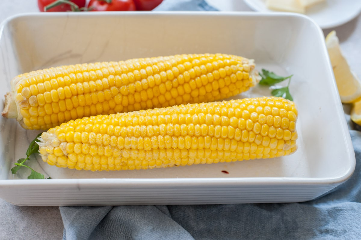 corn on the cob in a white baking dish