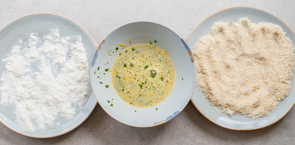 składniki na panierkę do kotletów rozłożone na 3 talerzach