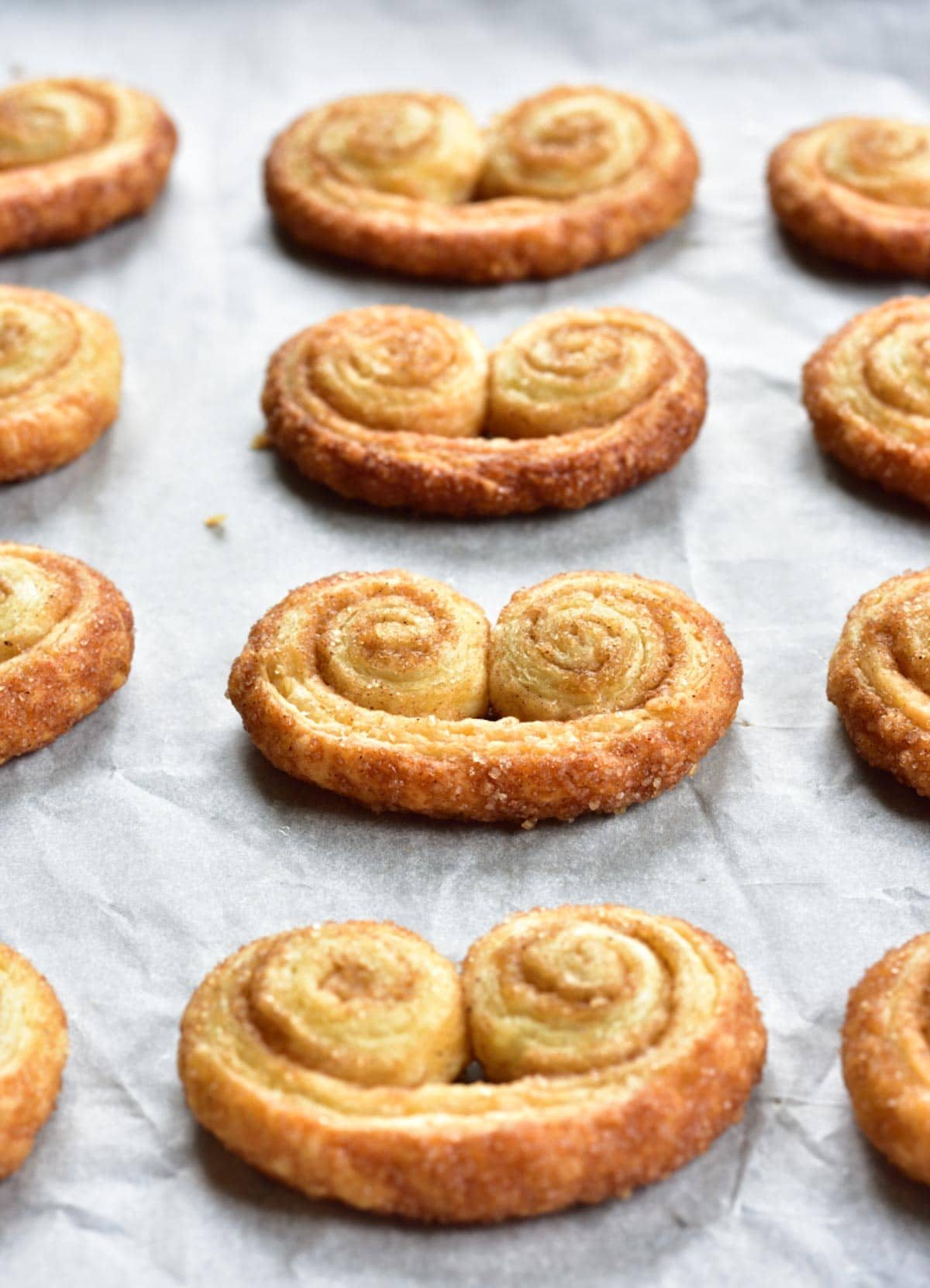 cinnamon palmiers on a baking paper sheet