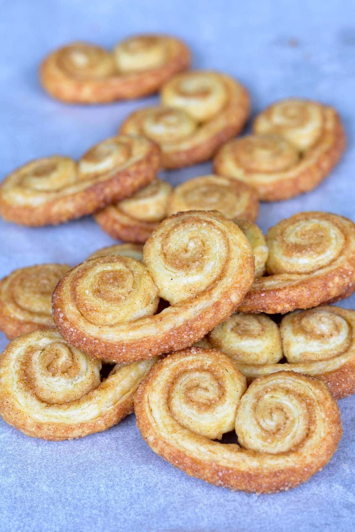 puff pastry cookies cinnamon palmiers on a blue background