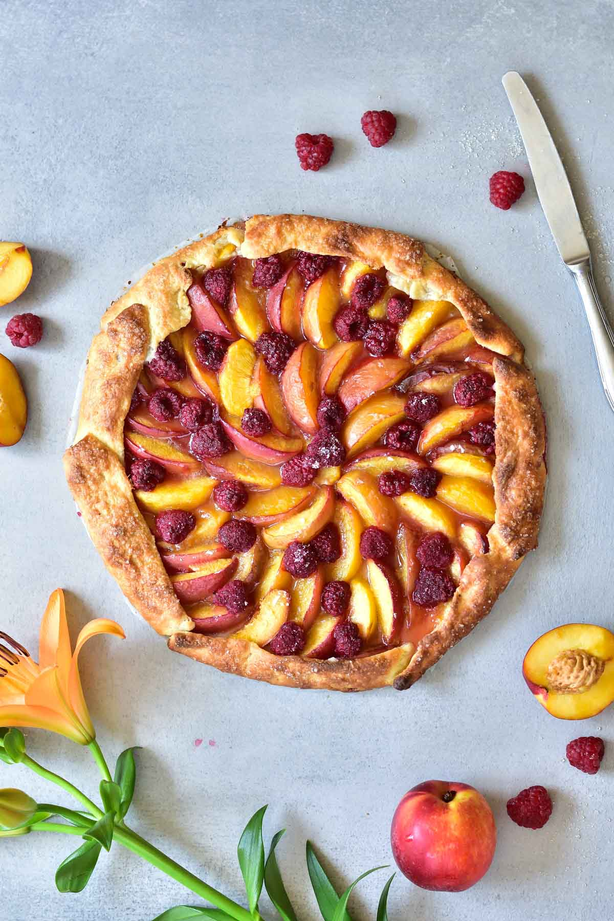 nectarine galette with raspberries on a blue background