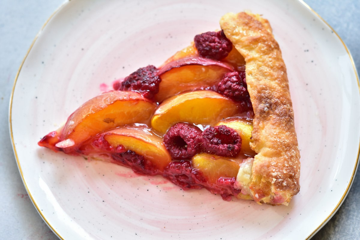 a piece of nectarine galette with raspberries on a rose plate