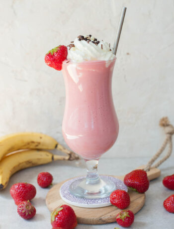strawberry banana milkshake in a high glass with whipped cream