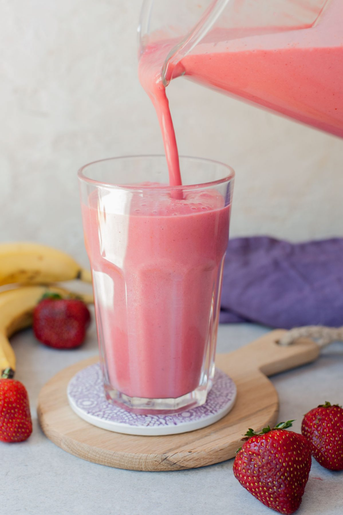 strawberry banana milkshake is being poured from a blender container to a high glass