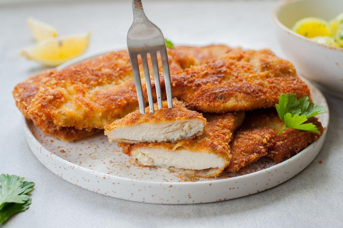 kotlety panierowane z kurczaka przekrojone na pół i nabite na widelec