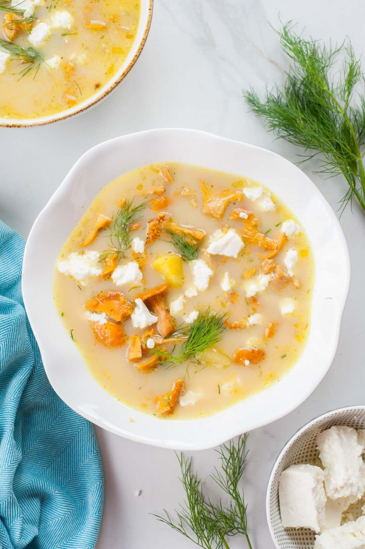 chanterelle soup in a white bowl, dill and a blue kitchen towel in the background