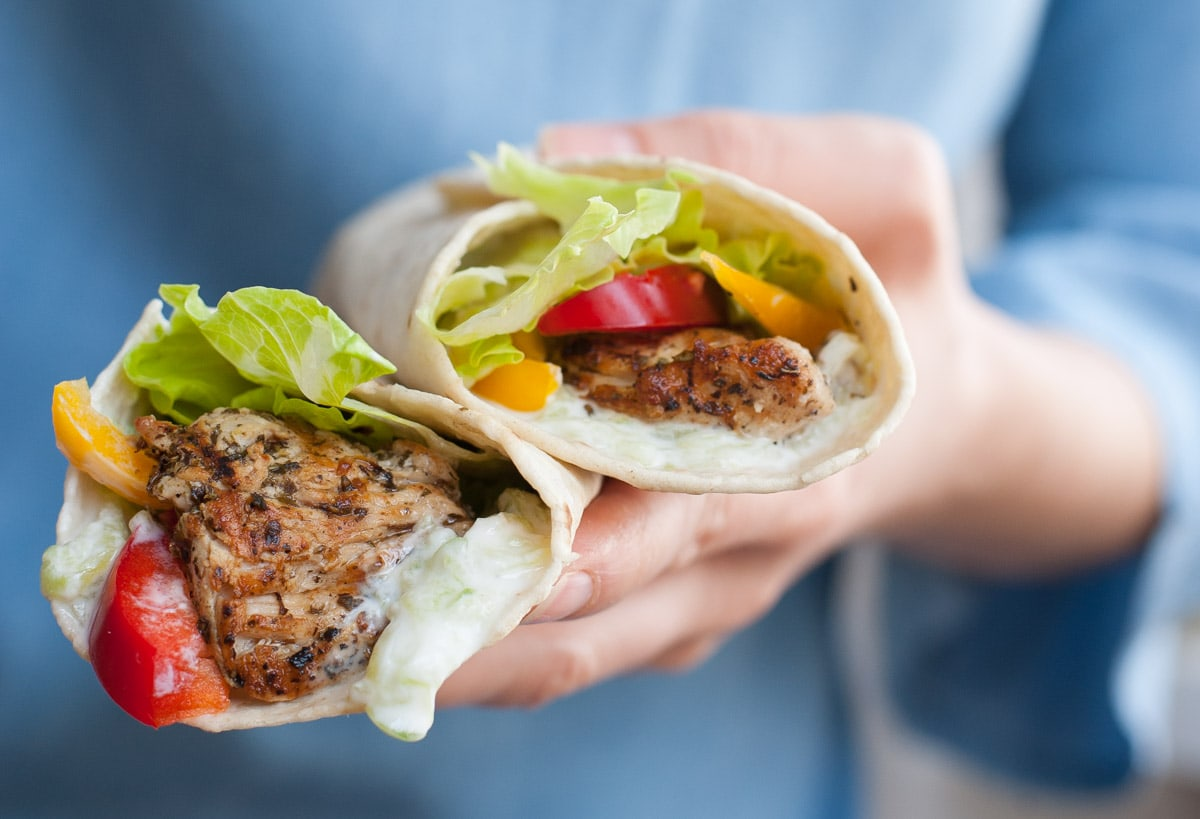 two Greek chicken wraps cut in half and held in hands