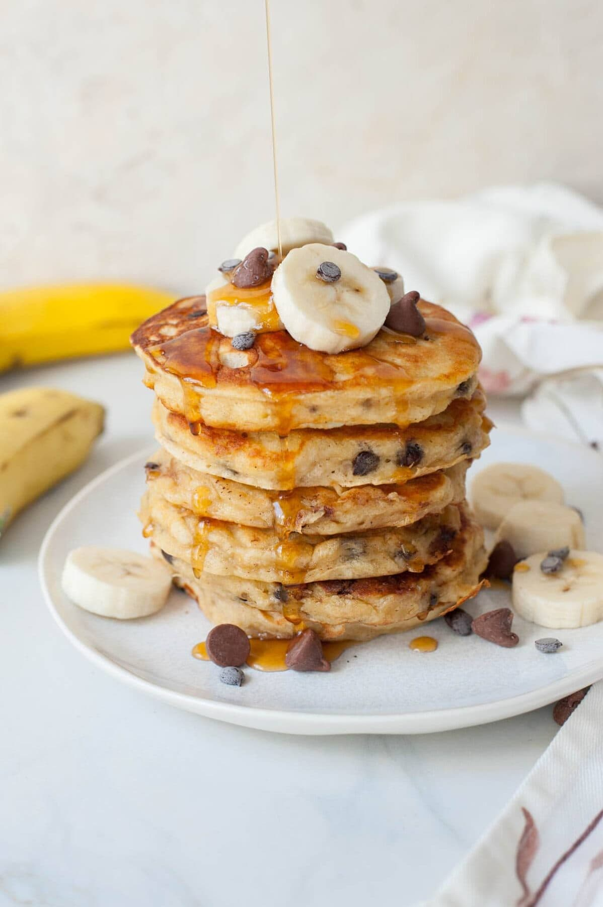 maple syrup is being poured over a stack of banana chocolate chip pancakes