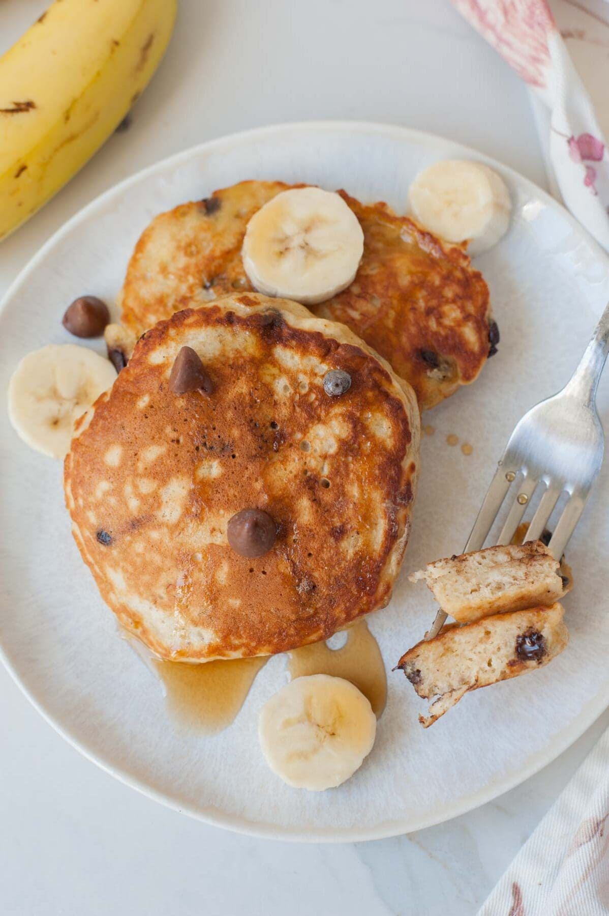 two banana chocolate chip pancakes on a white plate, fork and sliced bananas on the side