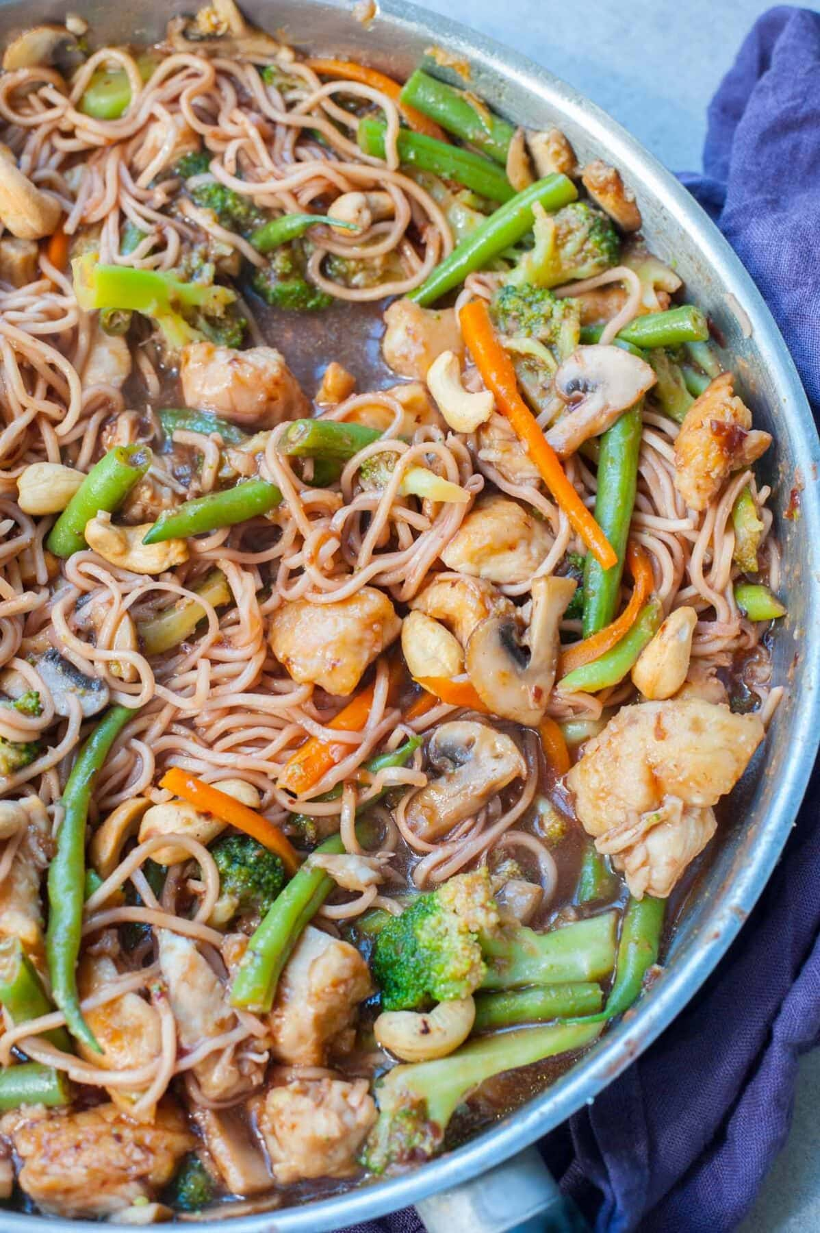 chicken, noodles, vegetables and Chinese plum sauce in a frying pan