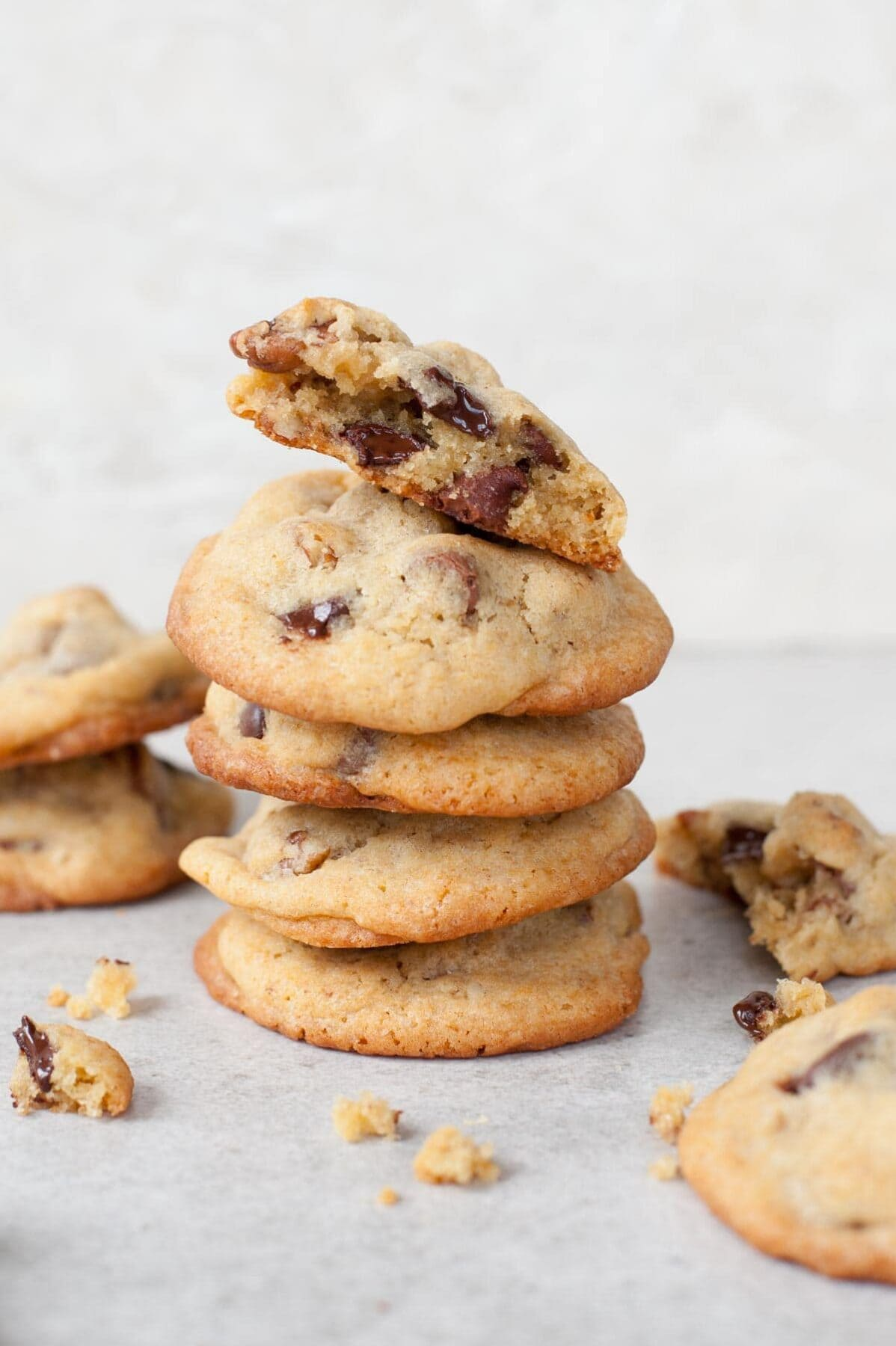 A stack of chocolate chip pecan cookies. Crumbled cookies in the foreground.
