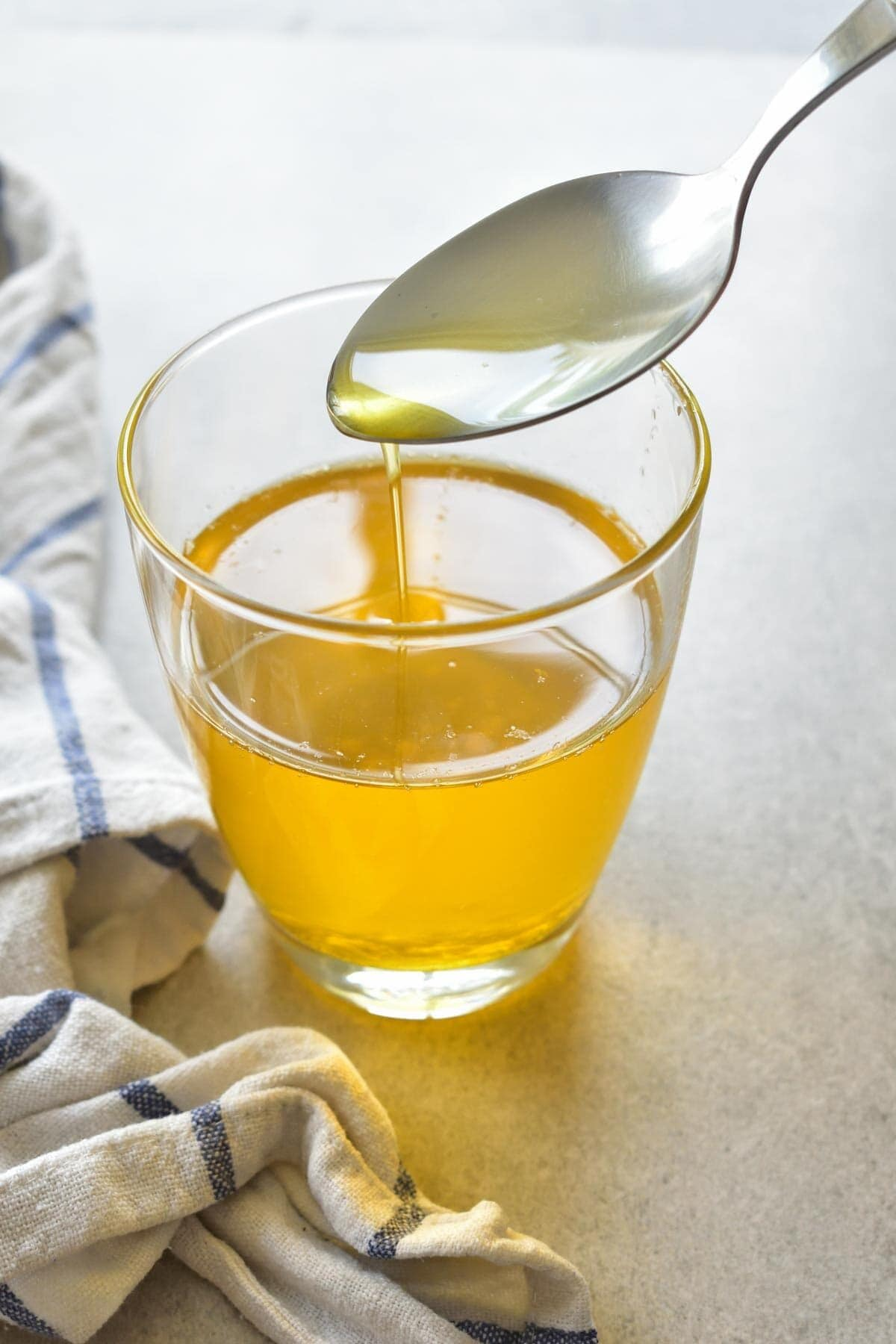 Clarified butter is being spooned into a glass.