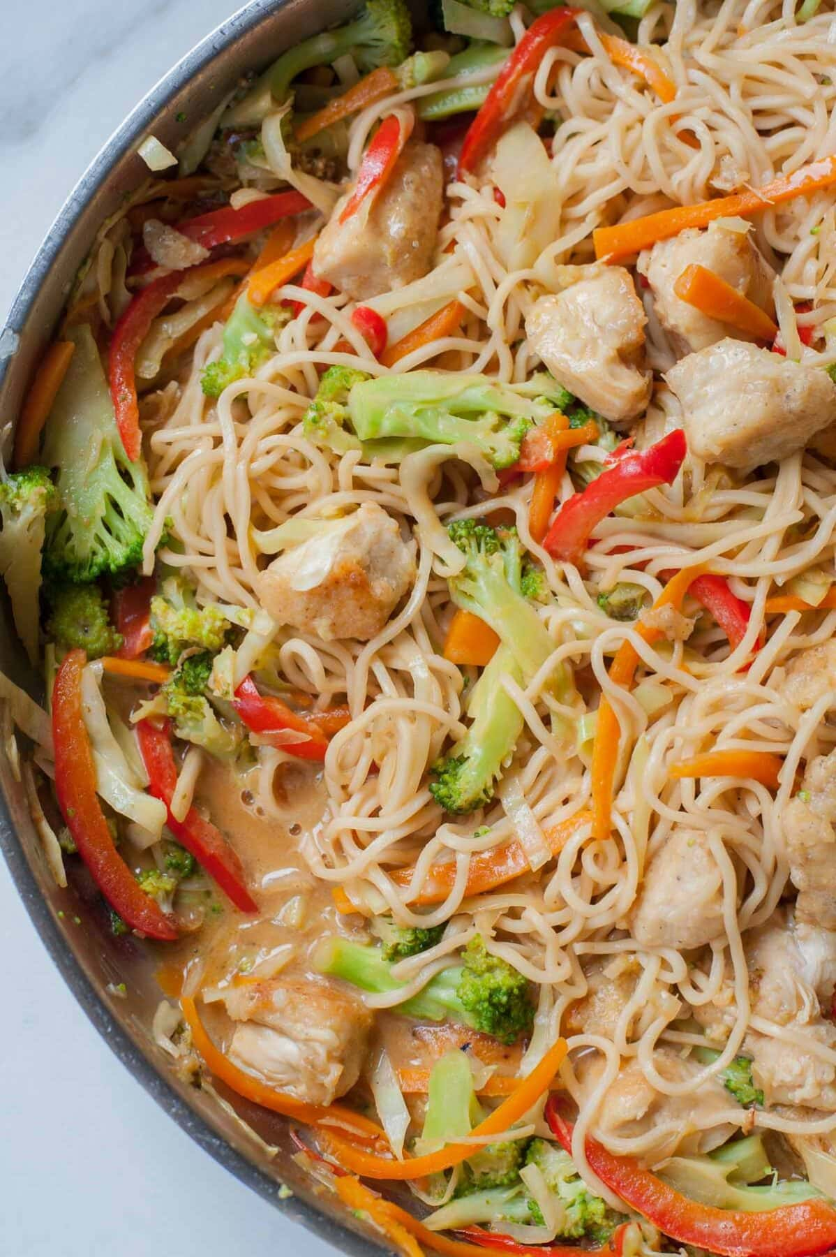 a closeup picture of peanut chicken noodles with vegetables in a frying pan