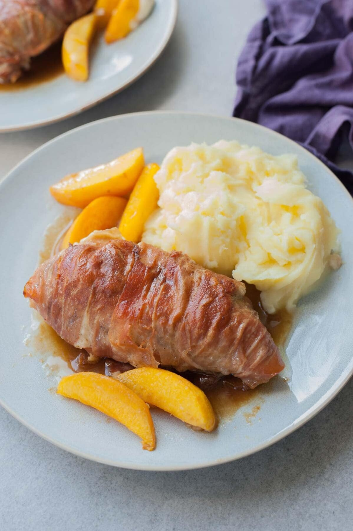 Prosciutto-wrapped chicken with peaches and balsamic glaze on a blue plate.