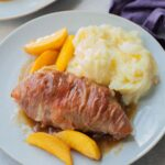 Prosciutto-wrapped chicken with peaches and mashed potatoes on a blue plate.