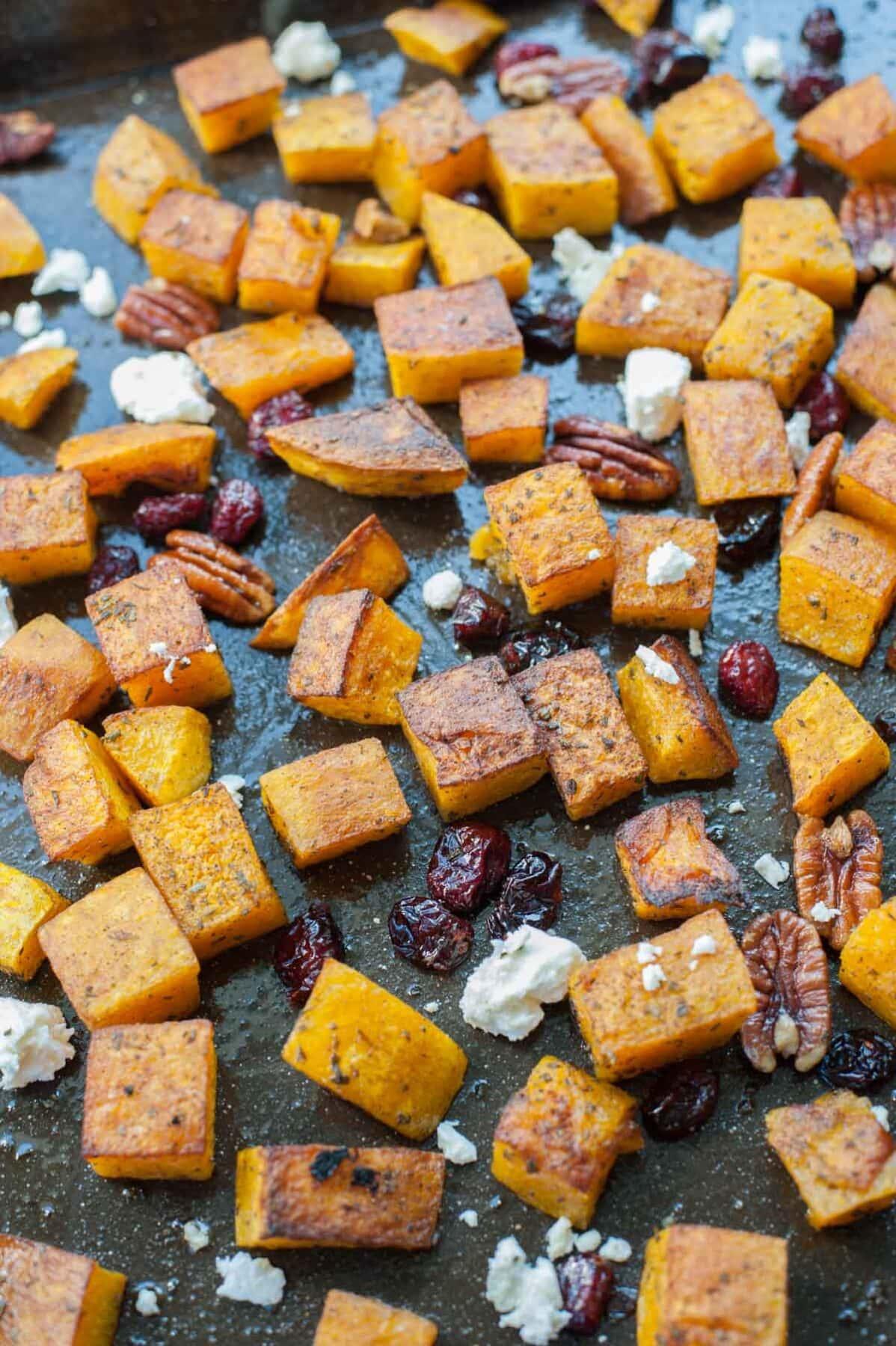 Pieczona dynia z rozmarynem, żurawiną, orzechami i serem feta na czarnej blaszce do pieczenia.