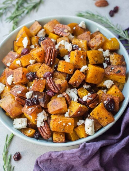 Roasted butternut squash with cranberries, pecans, rosemary and feta cheese in a blue bowl.
