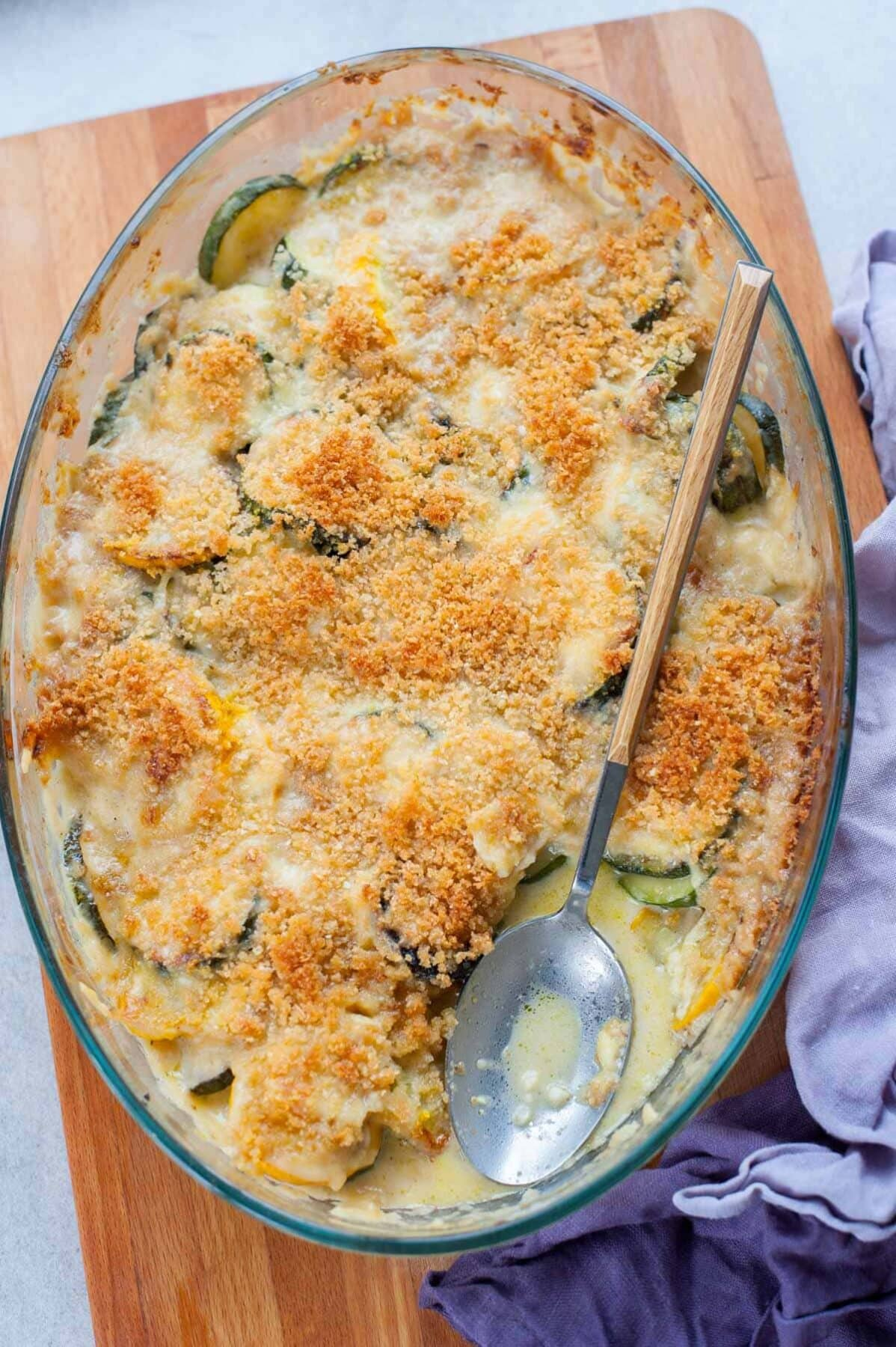 overhead picture of zucchini gratin in an oval glass baking dish on a chopping board