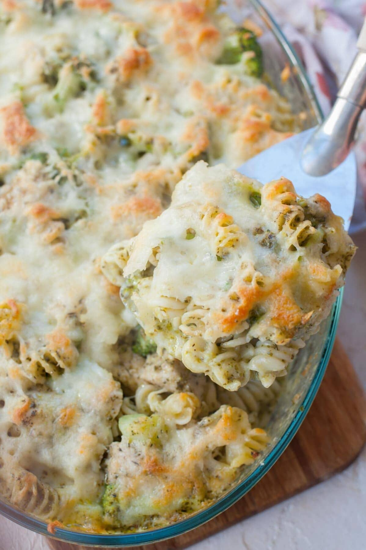Chicken pesto bake on a large spatula. Casserole dish in the background.