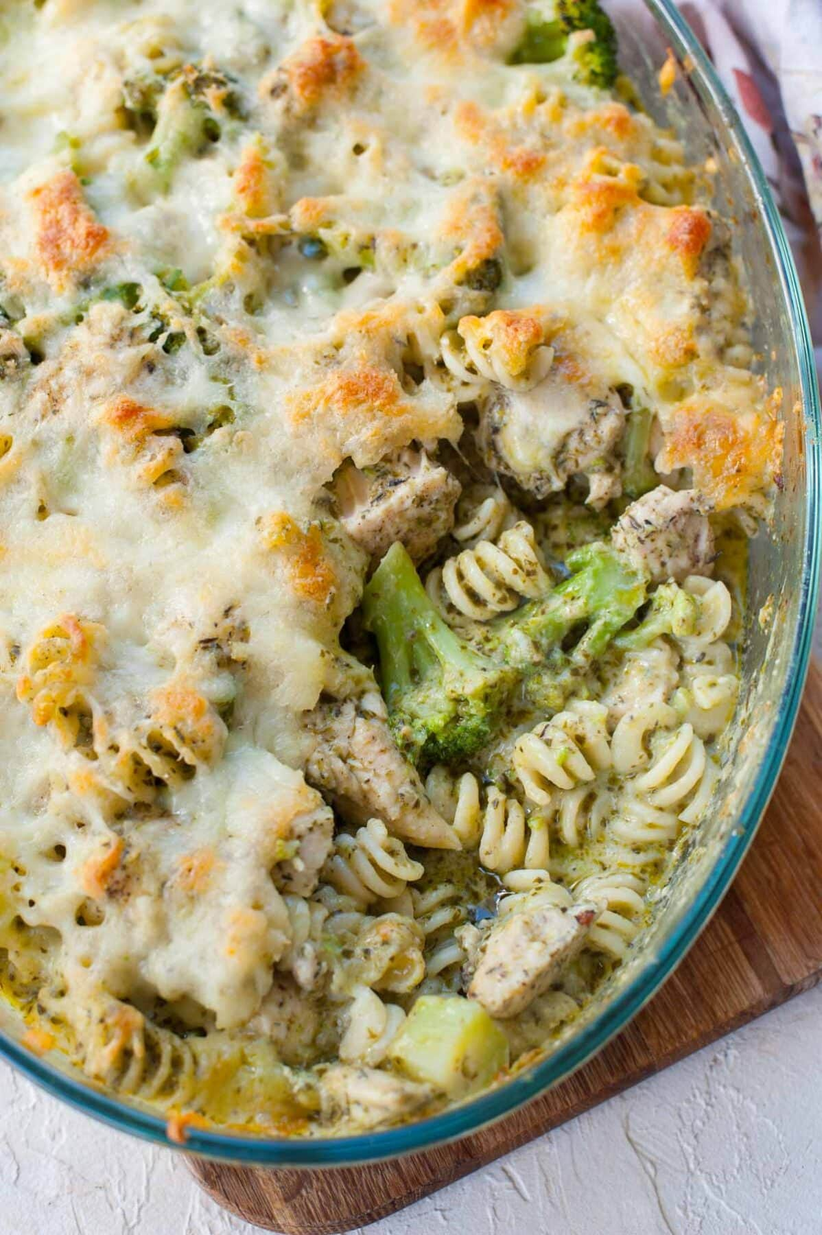Pesto chicken bake in a casserole dish with a serving missing.