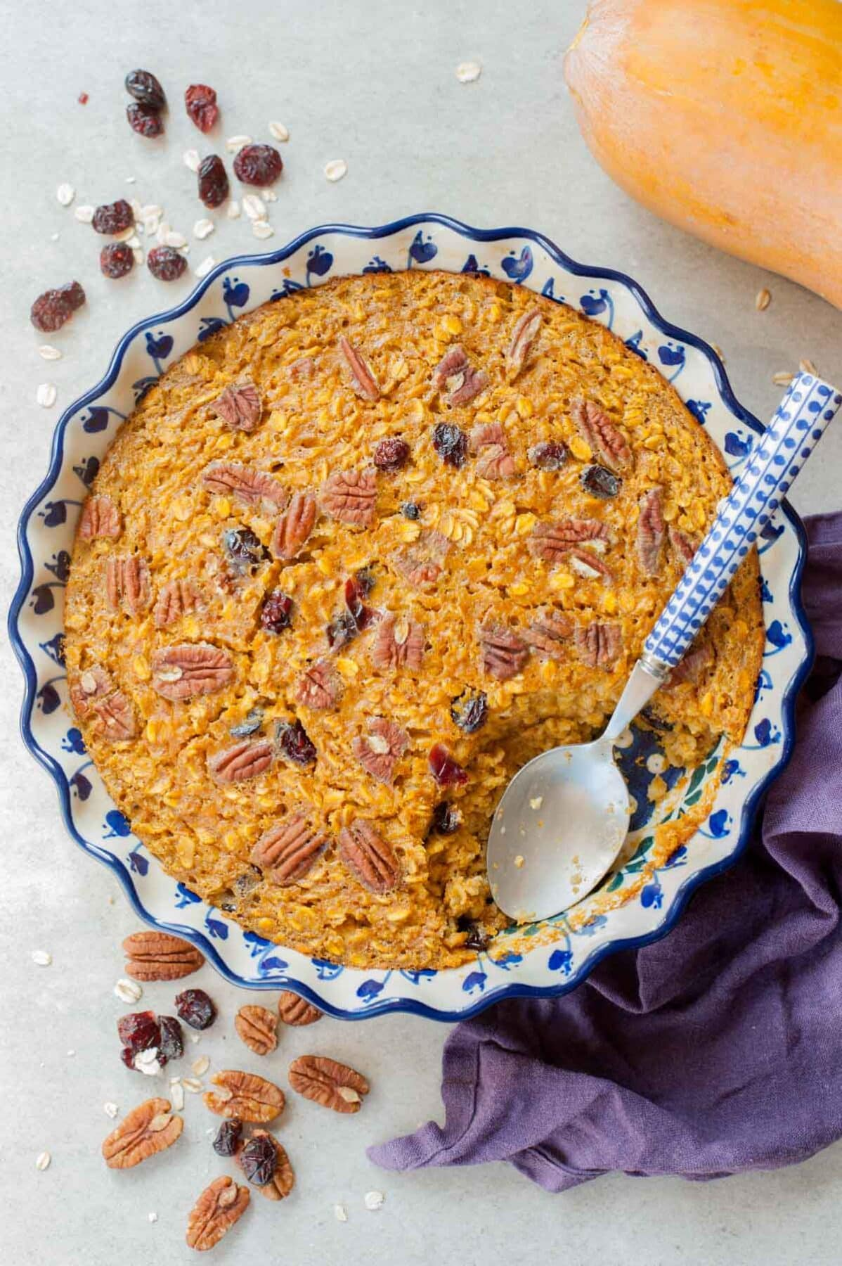 Baked pumpkin oatmeal in a blue-white baking dish. Kitchen cloth, pumpkin, pecans and cranberries in the background.