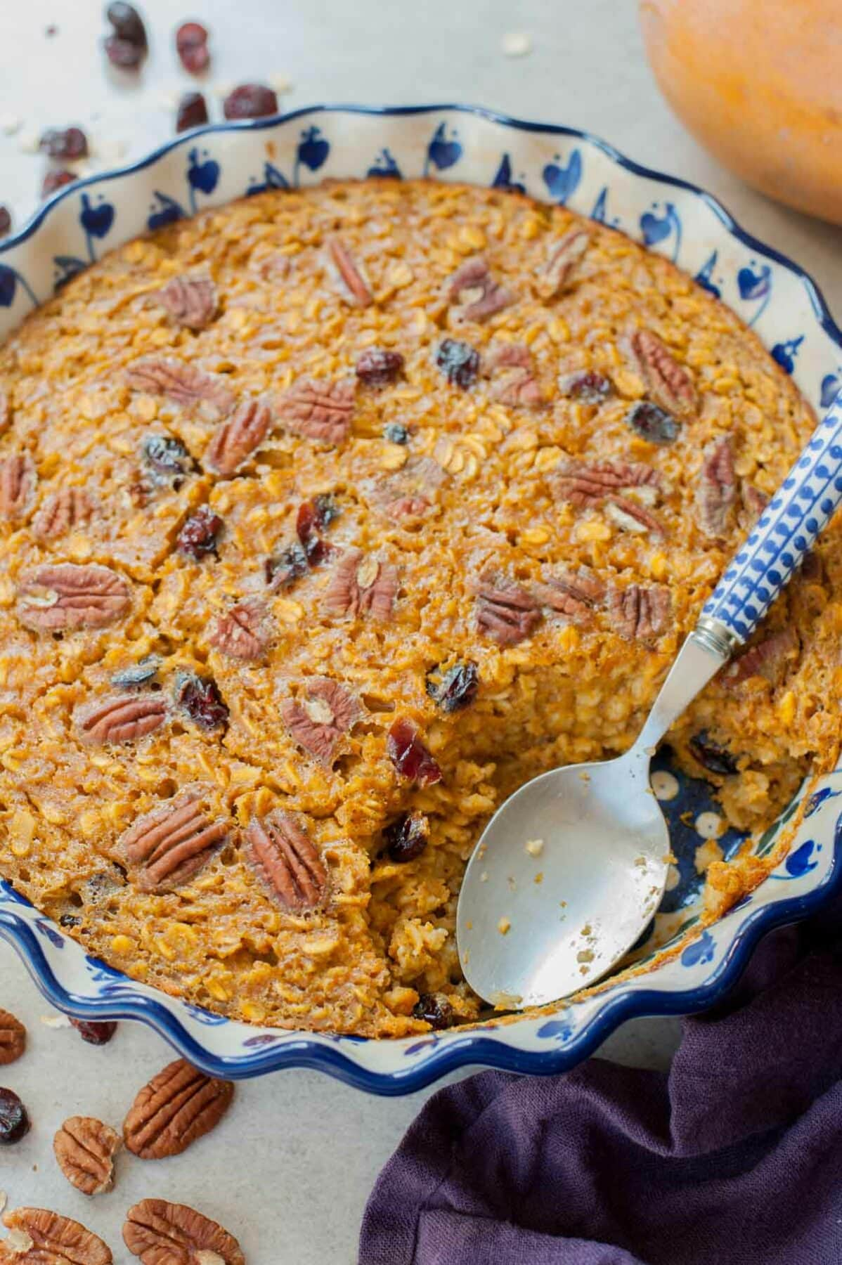 Close up picture of baked pumpkin oatmeal in a blue-white baking dish with a serving missing.