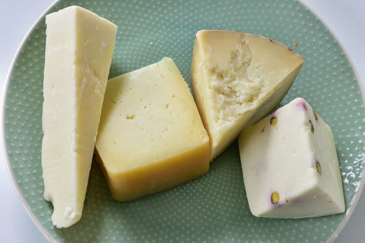 Different kinds of Pecorino cheese on a green plate.