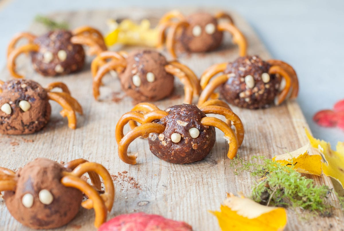 Pretzel spiders on a chopping board. Leaves scattered around.