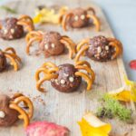 Pretzel spiders on a chopping board. Leaves in the background.